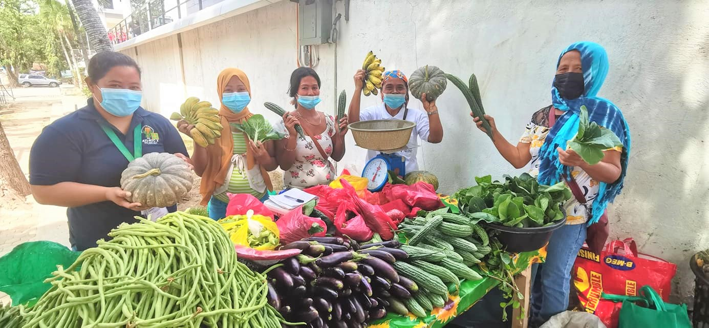 Helen J. Baa (second from right), Vice President of the Tag-Ilas Organic Vegetable Farmers Association, along with other women farmer members sell their organically-grown vegetables at the El Salvador City Hall. Joining the women farmers in the photo is Project Evaluation Officer I Cheriemy D. Generol.