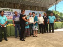 Dr. Luz Taposok in blue, receiving her certificate of appreciation from Kauswagan Mayor Rommel Arnado.