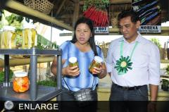 Ms. Desiree Duran showing her farm products to Director Asterio P. Saliot (Photo by Mr. Clemente Gabion)